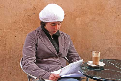 Woman drinking latte at sidewalk cafe in Roma